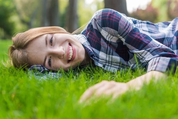 Menina sorridente, olhando para a câmera enquanto permanecer na grama Foto gratuita