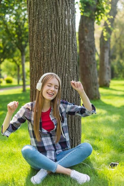 Menina sorridente, ouvir música enquanto está sentado na grama Foto gratuita