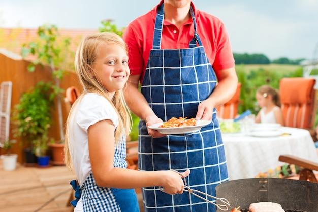 Menina sorridente, preparando o churrasco em família Foto Premium