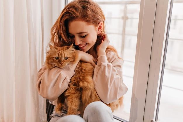 Menina sorridente relaxada brincando com seu gato fofo. foto interna da incrível senhora segurando o animal de estimação. Foto gratuita