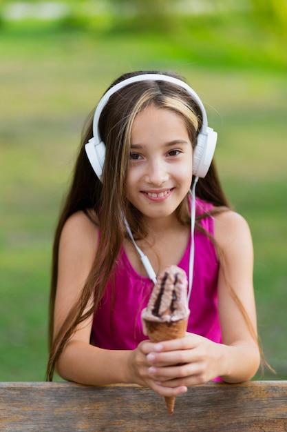 Menina sorridente, segurando, chocolate, casquinha sorvete Foto gratuita