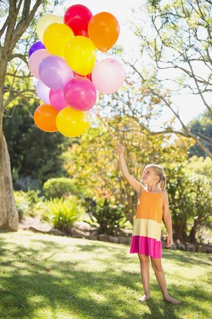 Menina sorridente segurando com balões no parque Foto Premium