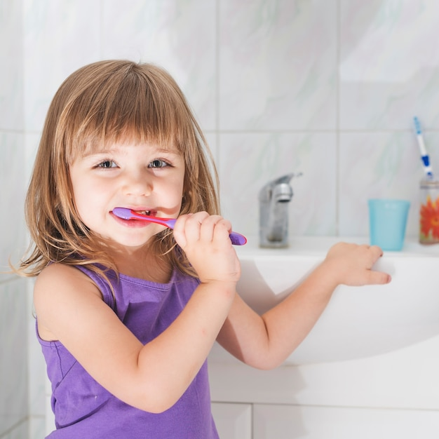 Menina sorridente, segurando, escova de dentes, ficar, frente, washroom, pia Foto gratuita