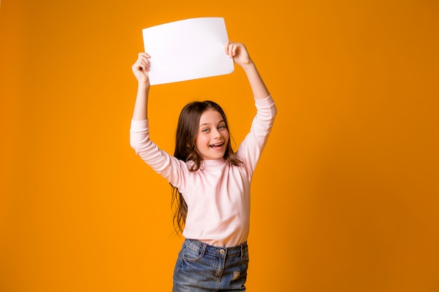 Menina sorridente segurando uma folha em branco sobre um fundo amarelo Foto Premium