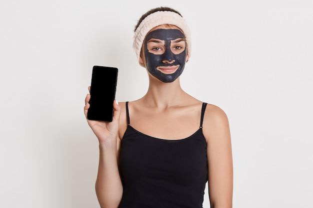 Menina sorridente, sendo fotografada após o banho, vestindo preto t shier e faixa de cabelo, isolada sobre a parede branca, mostrando o telefone inteligente com tela em branco. Foto Premium
