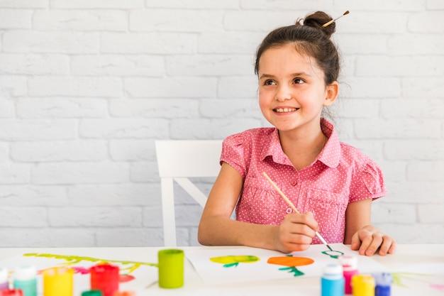 Menina sorridente, sentado na cadeira de pintura em papel branco com pincel Foto gratuita