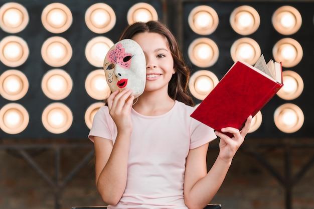 Menina sorridente, sentando, frente, luz fase, segurando máscara, e, livro Foto gratuita