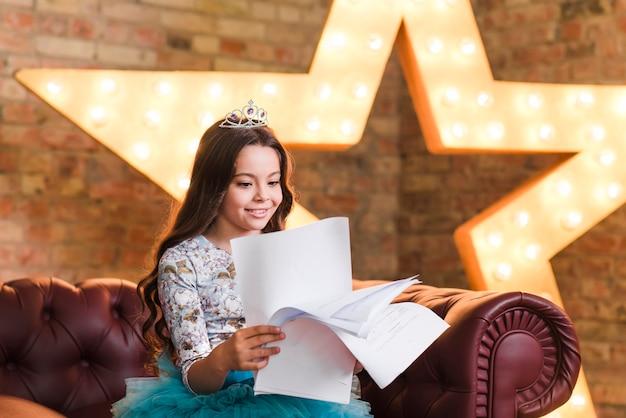 Menina sorridente, sentar sofá, leitura, scripts, contra, glowing, estrela, em, fundo Foto gratuita