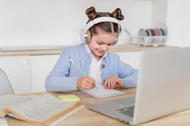 Menina sorridente, tendo uma aula on-line Foto gratuita