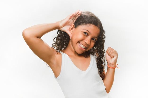 Menina sorridente tentando ouvir sobre fundo branco Foto gratuita