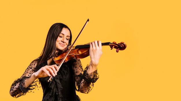 Menina sorridente tocando violino Foto gratuita