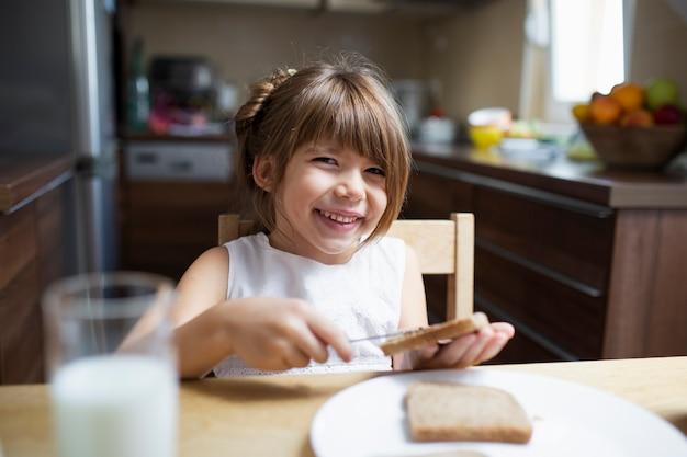Menina sorridente tomando café da manhã em casa Foto gratuita