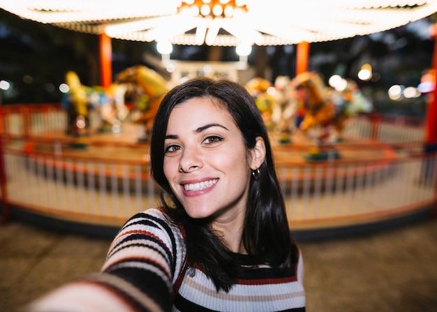 Menina sorridente tomando uma selfie Foto gratuita