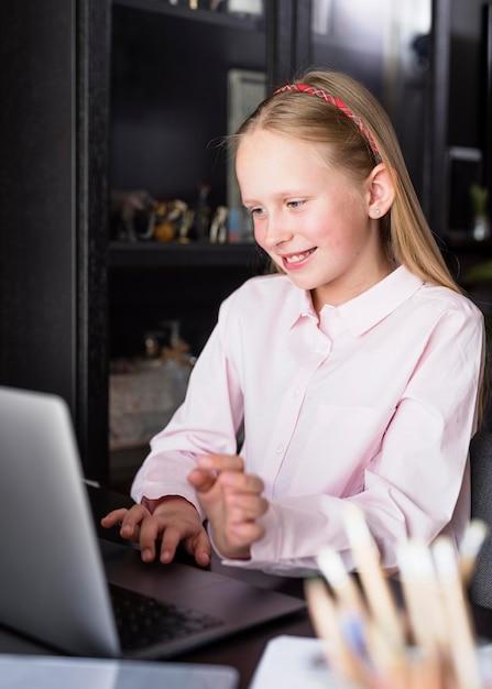 Menina sorridente usando o teclado Foto gratuita