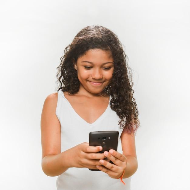 Menina sorridente, usando, telefone móvel Foto gratuita