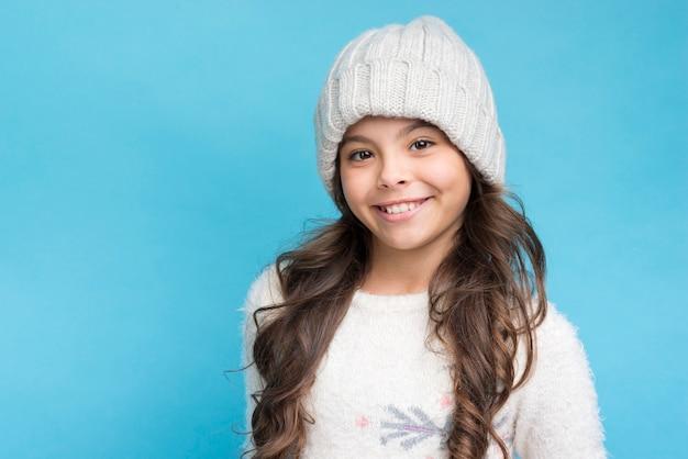 Menina sorridente, vestindo chapéu branco e roupas em fundo azul Foto gratuita