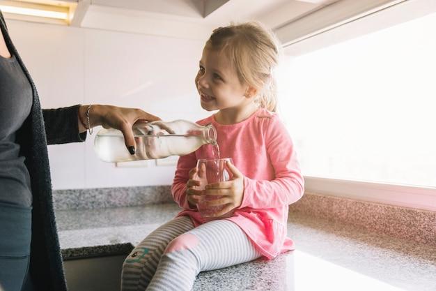 Menina sorridente, vidro segurando, enquanto, dela, mãe, água derramando Foto Premium