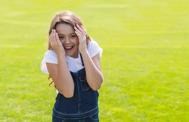 Menina sorrindo e brincando lá fora Foto gratuita