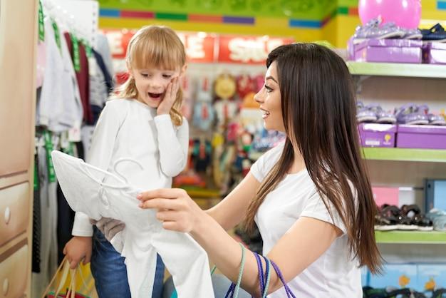 Menina sorrindo e olhando para novas roupas na grande loja Foto Premium