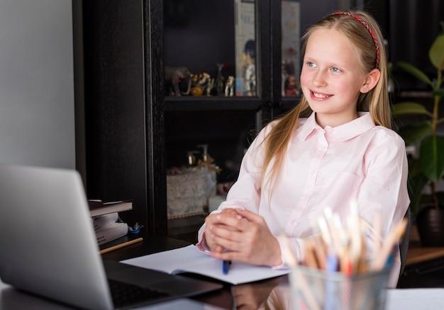 Menina sorrindo enquanto fazia uma aula on-line Foto gratuita