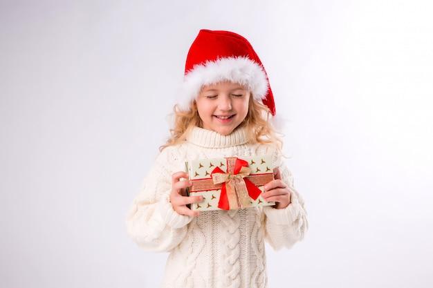 Menina sorrindo no chapéu de papai noel segurando a caixa de presente em fundo branco Foto Premium