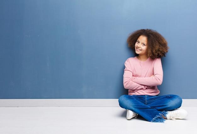 Menina sorrindo para a câmera com os braços cruzados e uma expressão feliz, confiante e satisfeita, vista lateral, sentada no chão Foto Premium