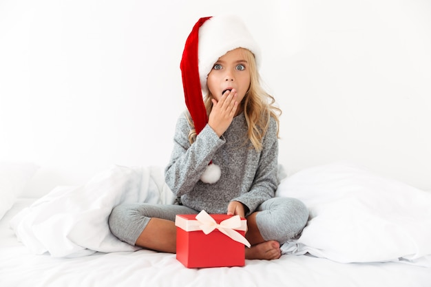 Menina surpreendida no chapéu de papai noel segurando presente enquanto está sentado com as pernas cruzadas na cama Foto gratuita