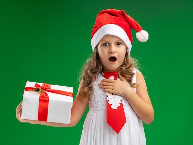 Menina surpresa com chapéu de natal com gravata segurando uma caixa de presente e colocando a mão em si mesma isolada sobre fundo verde Foto gratuita