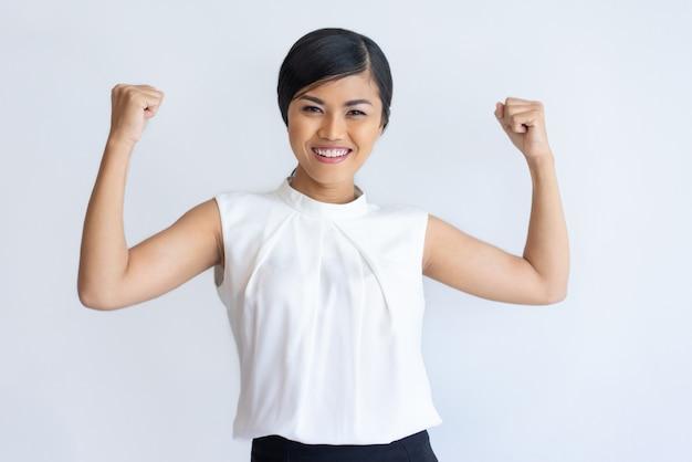 Menina tailandesa alegre mostrando força Foto gratuita