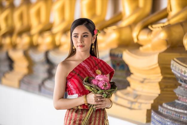 Menina tailandesa na mão tailandesa tradicional do traje que guarda lótus no templo tailandês, cultura da identidade de tailândia. Foto Premium