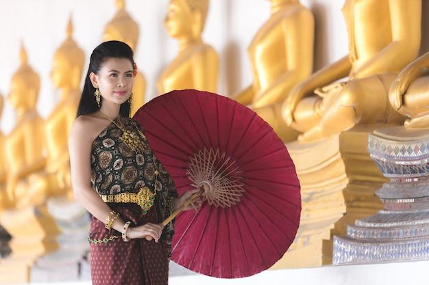 Menina tailandesa no traje tailandês tradicional com o guarda-chuva vermelho no templo tailandês, cultura da identidade de tailândia. Foto Premium