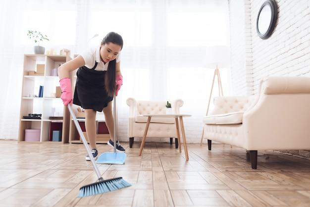 Menina tailandesa varrer o chão com vassoura e colher. Foto Premium