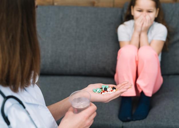 Menina tem medo de seu médico feminino dando remédio e copo de água na mão Foto gratuita