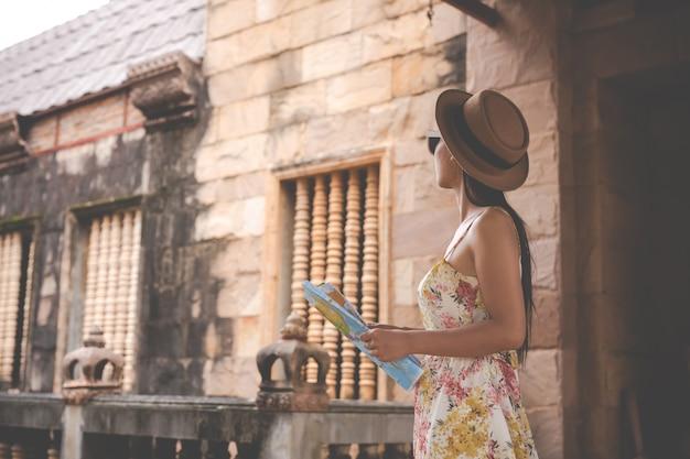 Menina tem um mapa turístico na cidade velha. Foto gratuita