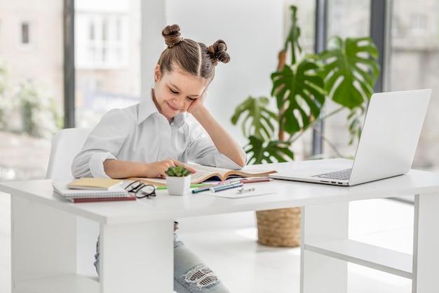 Menina tendo uma aula on-line em casa Foto gratuita