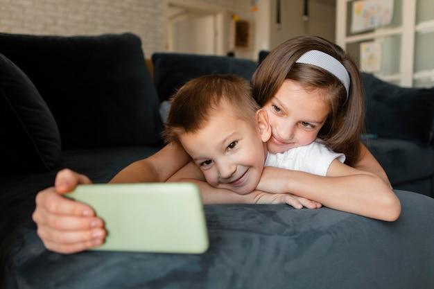 Menina tirando uma selfie em casa com o irmão Foto Premium