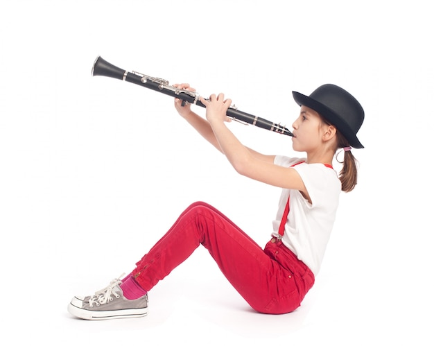 Menina tocando clarinete em um fundo branco Foto Premium