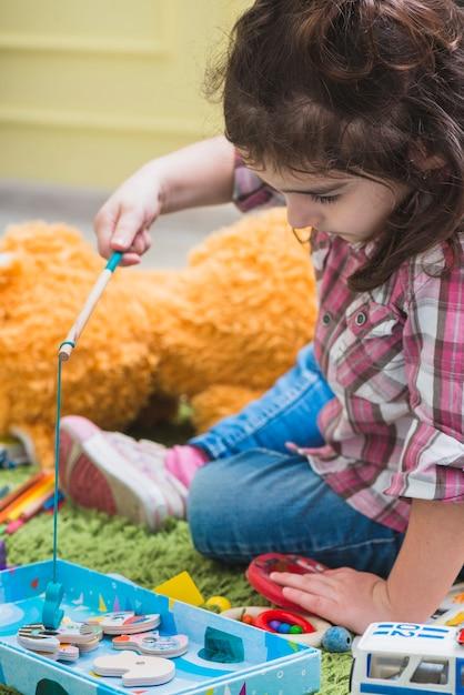 Menina, tocando, com, brinquedo, cana de pesca Foto gratuita