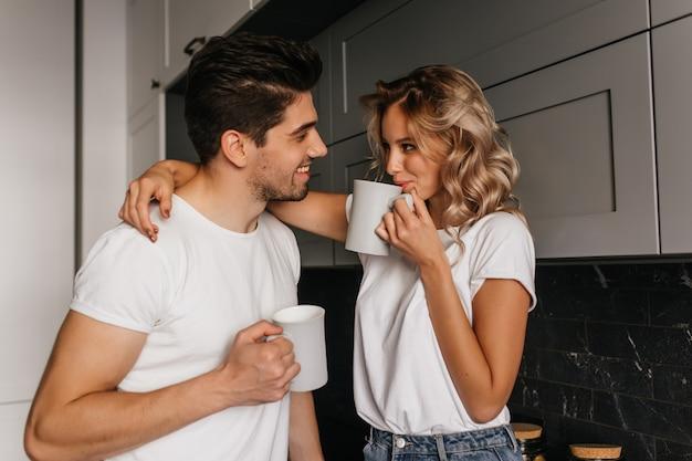 Menina tocando o marido de brincadeira e bebendo café. retrato interior de casal romântico tomando café da manhã juntos. Foto gratuita