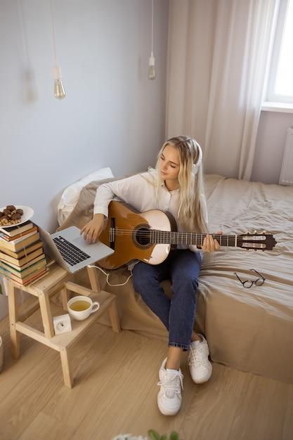 Menina tocando violão em casa Foto Premium