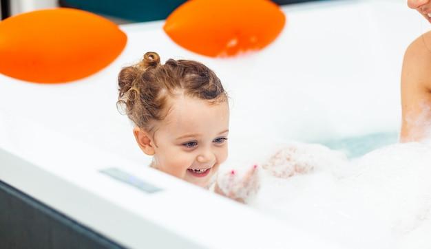Menina toma banho em uma banheira de hidromassagem. Foto Premium