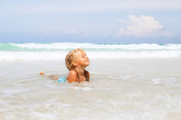 Menina toma banho no mar na praia com areia branca Foto Premium