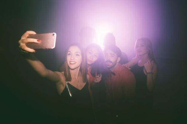 Menina tomando selfie na boate Foto gratuita