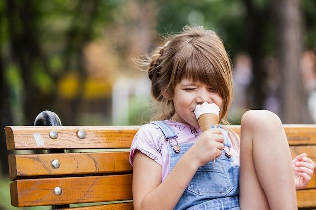 Menina tomando sorvete sentado no banco Foto gratuita