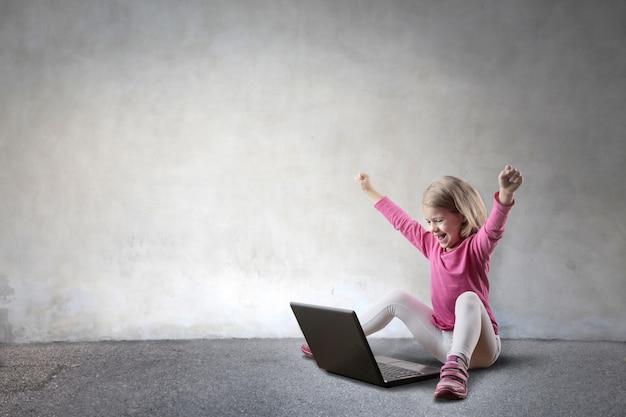Menina torcendo e olhando para um laptop Foto Premium