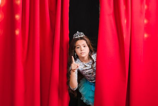 Menina triste em pé atrás da cortina vermelha gesticulando Foto gratuita