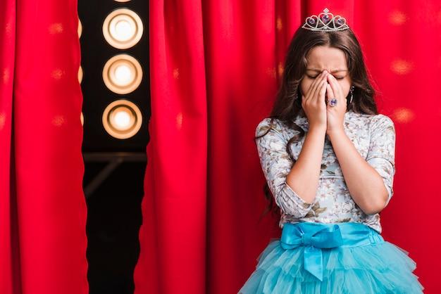 Menina triste em pé atrás da cortina vermelha Foto gratuita