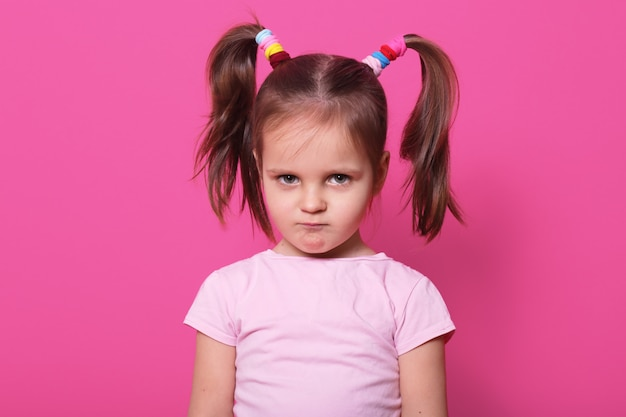 Menina triste fica na parede rosa. garoto bonito usa camiseta rosa, tem duas caudas de pônei fanny com muitos scrunchies coloridos, parece machucado com lábios carnudos. criança chateada no playground. Foto gratuita