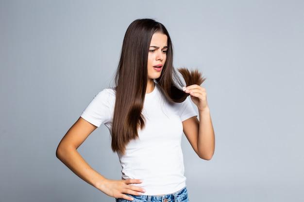 Menina triste, olhando para os cabelos danificados, isolado no branco Foto gratuita