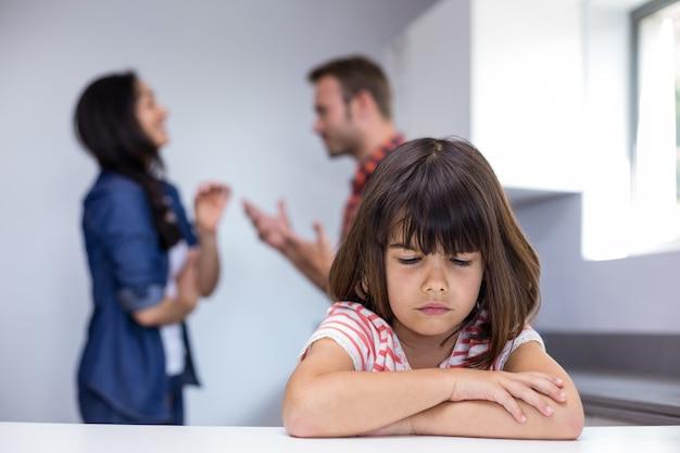 Menina triste ouvir seus pais discutindo Foto Premium